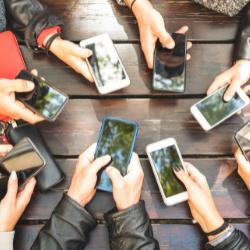 Multiple hands holsing mobile phones